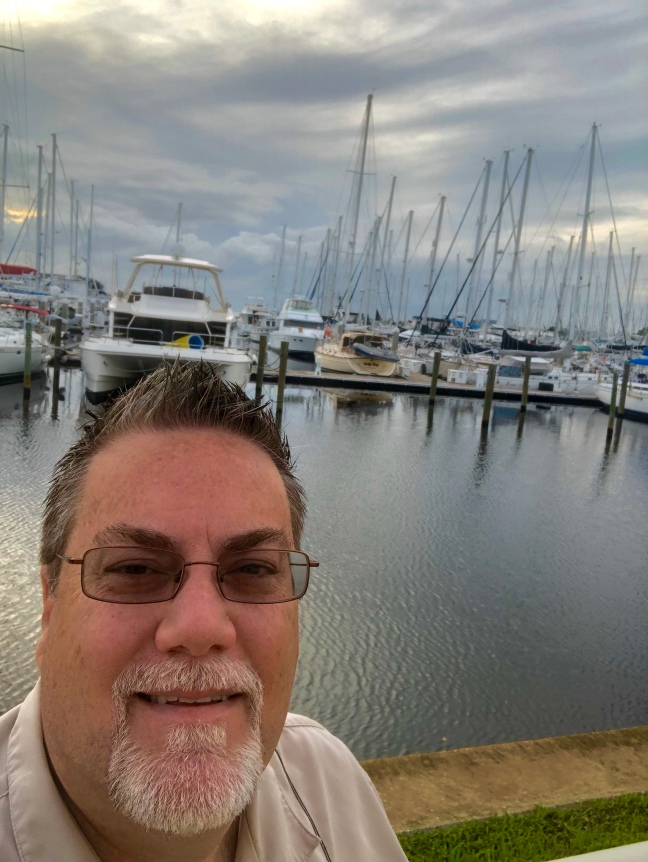 David Brodosi standing by sailboats in Bayboro Harbor