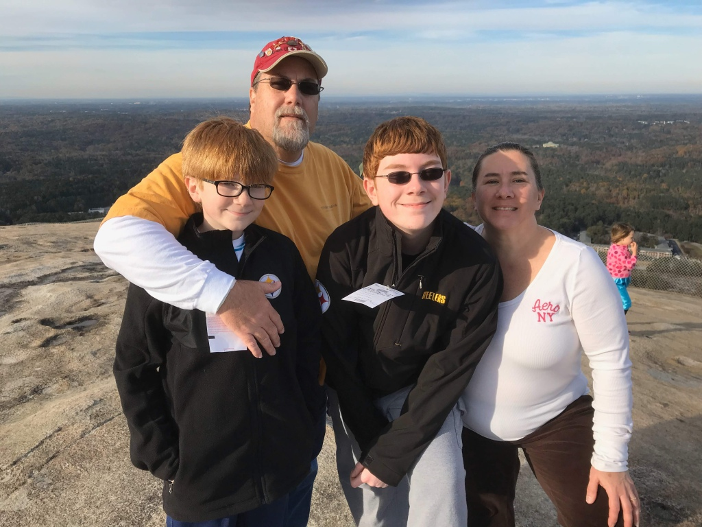 A photo of David Brodosi and his family on top of the mountain